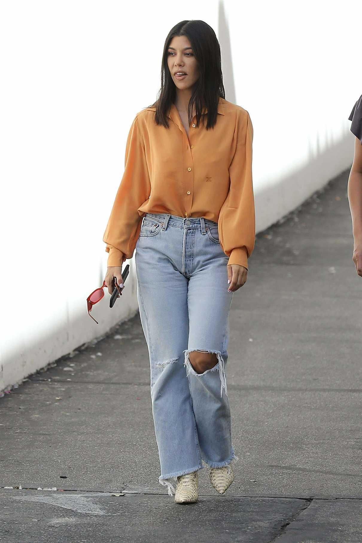 Kourtney Kardashian ia an Orange Blouse