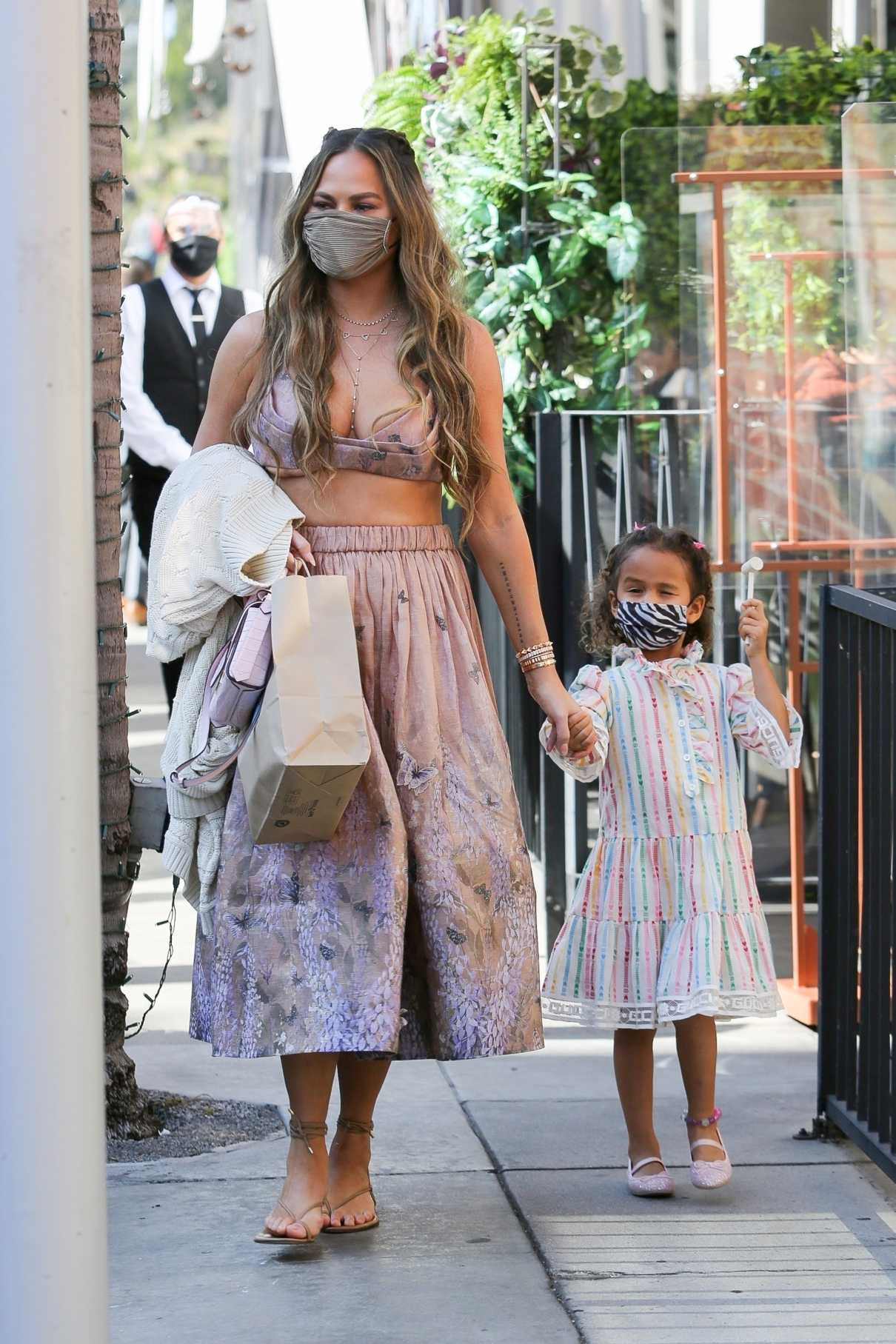 Chrissy Teigen in an Olive Protective Mask